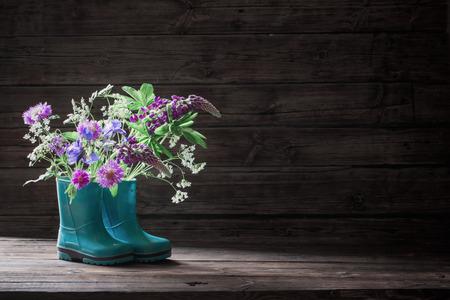 summer flowers in rubber boots on old dark wooden background Banco de Imagens