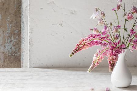 pink summer flowers in white vase on white old background Banco de Imagens