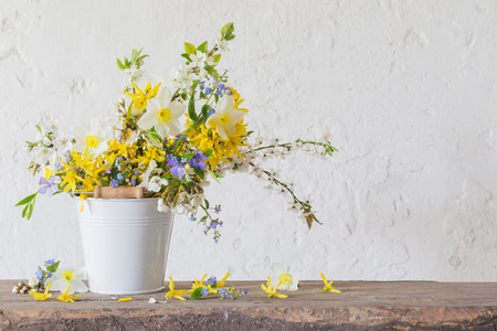 spring flowers in white bucket on old wooden table Standard-Bild - 124556168