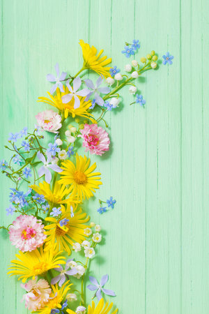 frame of beautiful flowers on green wooden background