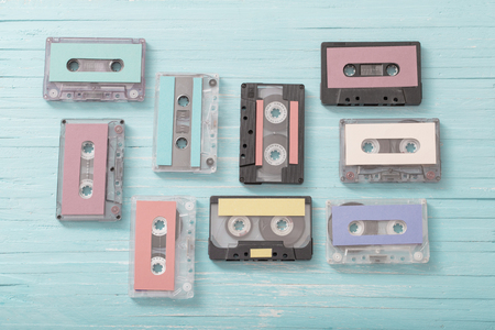 Old plastic cassette on blue wooden background. Retro music concept
