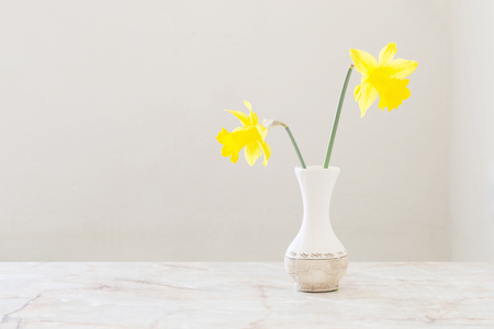 yellow daffodils in vase on marble table