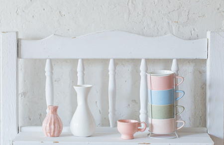cups and vase  on vintage white shelf