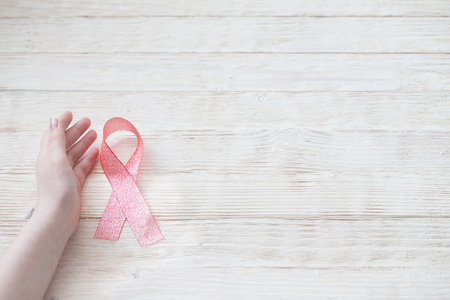 pink ribbon in hand as  symbol of fighting breast cancer