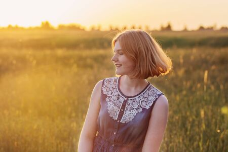 teenager girl in summer field at sunset
