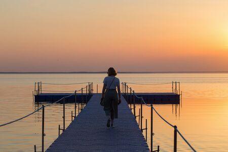girl on pontoon pier at sunset 스톡 콘텐츠