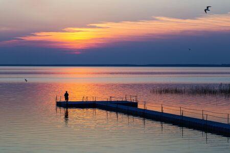 men on pontoon pier at sunset