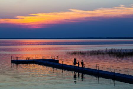 family on pontoon pier at sunset