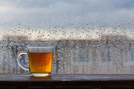 cup of tea on  background of  window with raindrops at sunset 스톡 콘텐츠