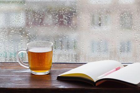 filiżanka herbaty na tle okna z kroplami deszczu o zachodzie słońca