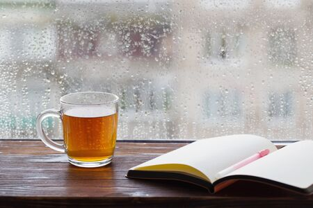 Taza de té en el fondo de la ventana con gotas de lluvia al atardecer