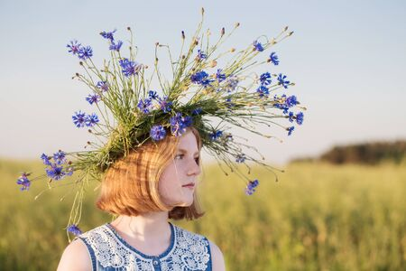 beautiful teenager girl in summer field with cornflower Reklamní fotografie