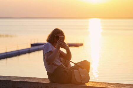 smiling girl making selfie on  background of  sunset on  sea