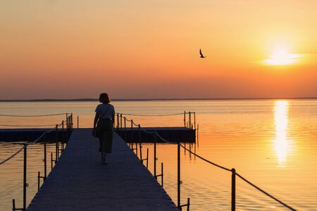girl on pontoon pier at sunset Stock Photo