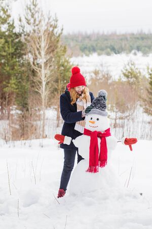happy teenager girl with snowman in winter forest 스톡 콘텐츠