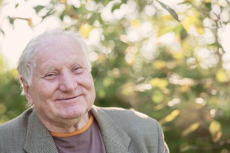 portrait of  elderly man in sunny park
