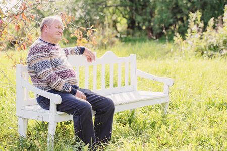 elderly man resting on white wooden bench in autumn park Stock Photo