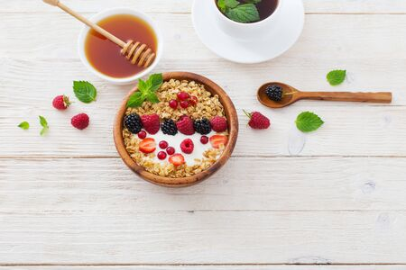 the granola with berries on white wooden background Reklamní fotografie