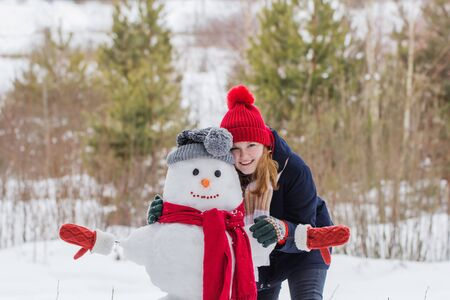 happy teenager girl with snowman in winter forest Stok Fotoğraf