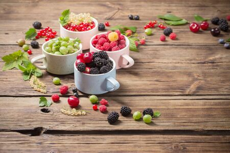 different berries on old wooden background