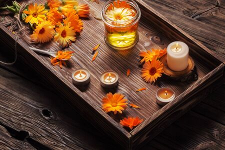 Medicinal flowers of calendula and  aroma oil with burning candles on tray   on dark wooden background 免版税图像