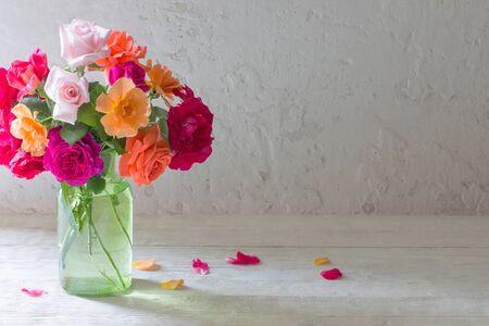 Rosas en jarrón sobre fondo de pared blanca