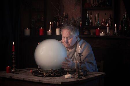 älterer Zauberer mit Kristallkugel