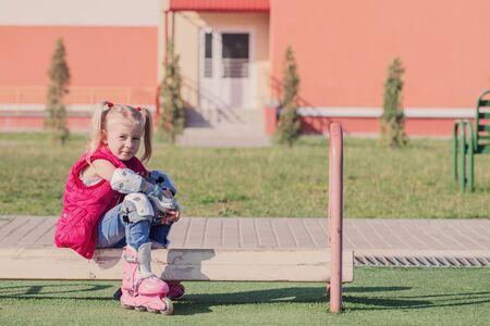little girl sitting on bench in playground in roller skates