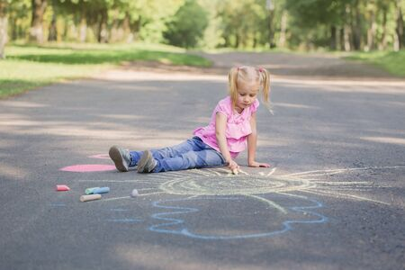 little girl draws with chalk on  pavement Stock fotó