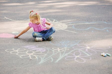 little girl draws with chalk on  pavement 스톡 콘텐츠