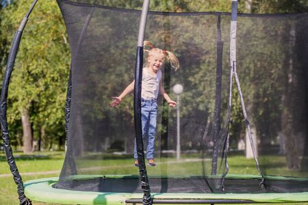girl jumping on trampoline in park