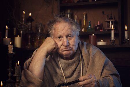 elderly alchemist monk with rosary Imagens