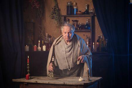 älterer Alchemistenmönch mit Kerze