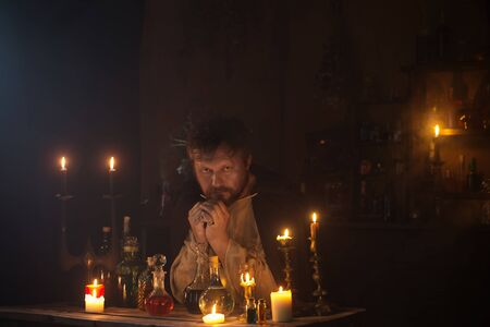 portrait of  wizard with burning candles and magic potions Imagens