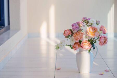 beautiful roses in ceramic white jug on floor