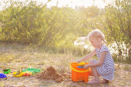 little girl play on sand with toys by river Zdjęcie Seryjne