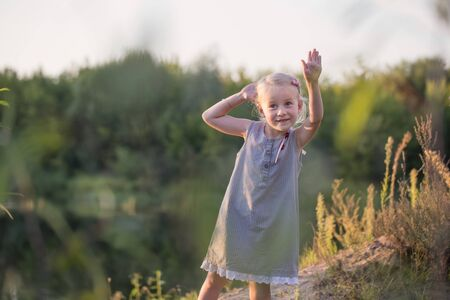 beautiful little blonde girl on summer sunset beach Stock fotó