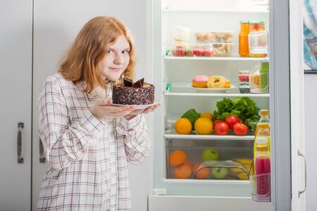 smile teenager girl at fridge with chocolate cake