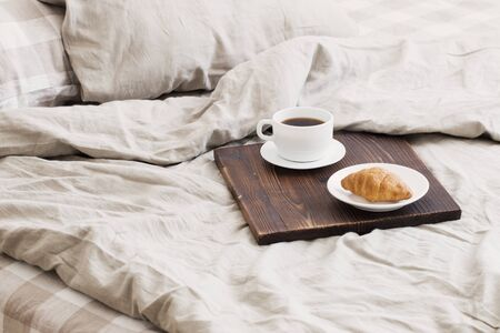 coffee on wooden  tray on the bed in bedroom