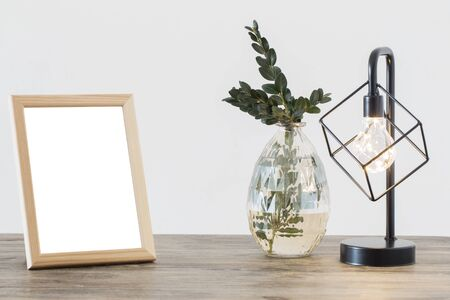 metal black lamp and wooden frame in white interior