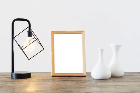 metal black lamp, vases and wooden frame  in white interior