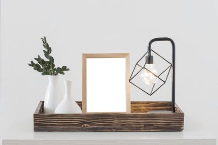 metal black lamp and wooden frame  in white interior Фото со стока - 129781256