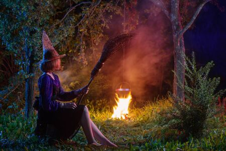 young witch by  fire in night forest makes in cauldron magic potion