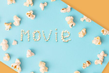 word movie made of popcorn on  blue and orange background