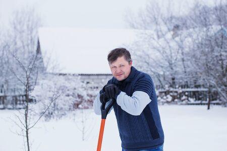 mature man cleans snow shovel Banco de Imagens