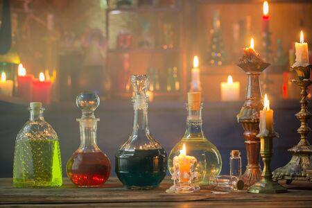 Pociones mágicas en botellas sobre fondo de madera Foto de archivo