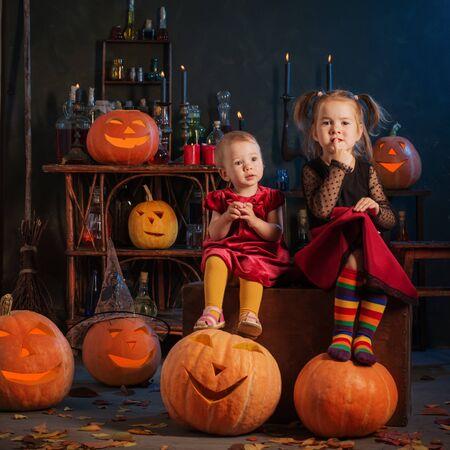 dos pequeñas brujas con calabazas de Halloween en el interior