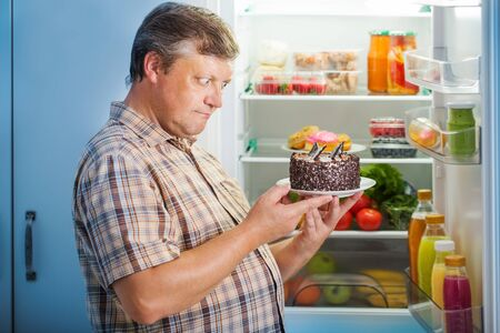 Reife Männer am Kühlschrank mit Essen Standard-Bild