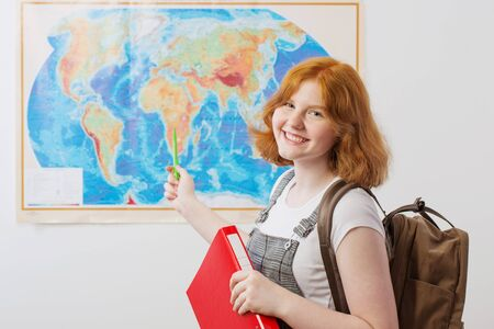 teen girl stands at  geographical map 写真素材