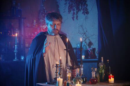 portrait of  wizard with burning candles and magic potions Banco de Imagens